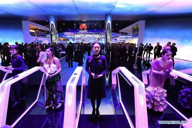 Les gens visitent le stand de Huawei lors de la première journée du Mobile World Congress