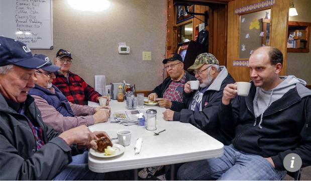 Capture le fermier Brad Te Grootenhuis, à droite, est assis avec des habitués de la foule au café Boxcars à Hospers, en Iowa