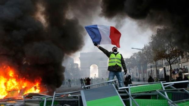 Un manifestant agite le drapeau français sur une barricade en feu sur les Champs-Élysées